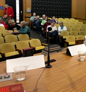 Photo shows audience of men and women seated in the city council chambers before the talk begins, with the book Cork Wars in the foreground.