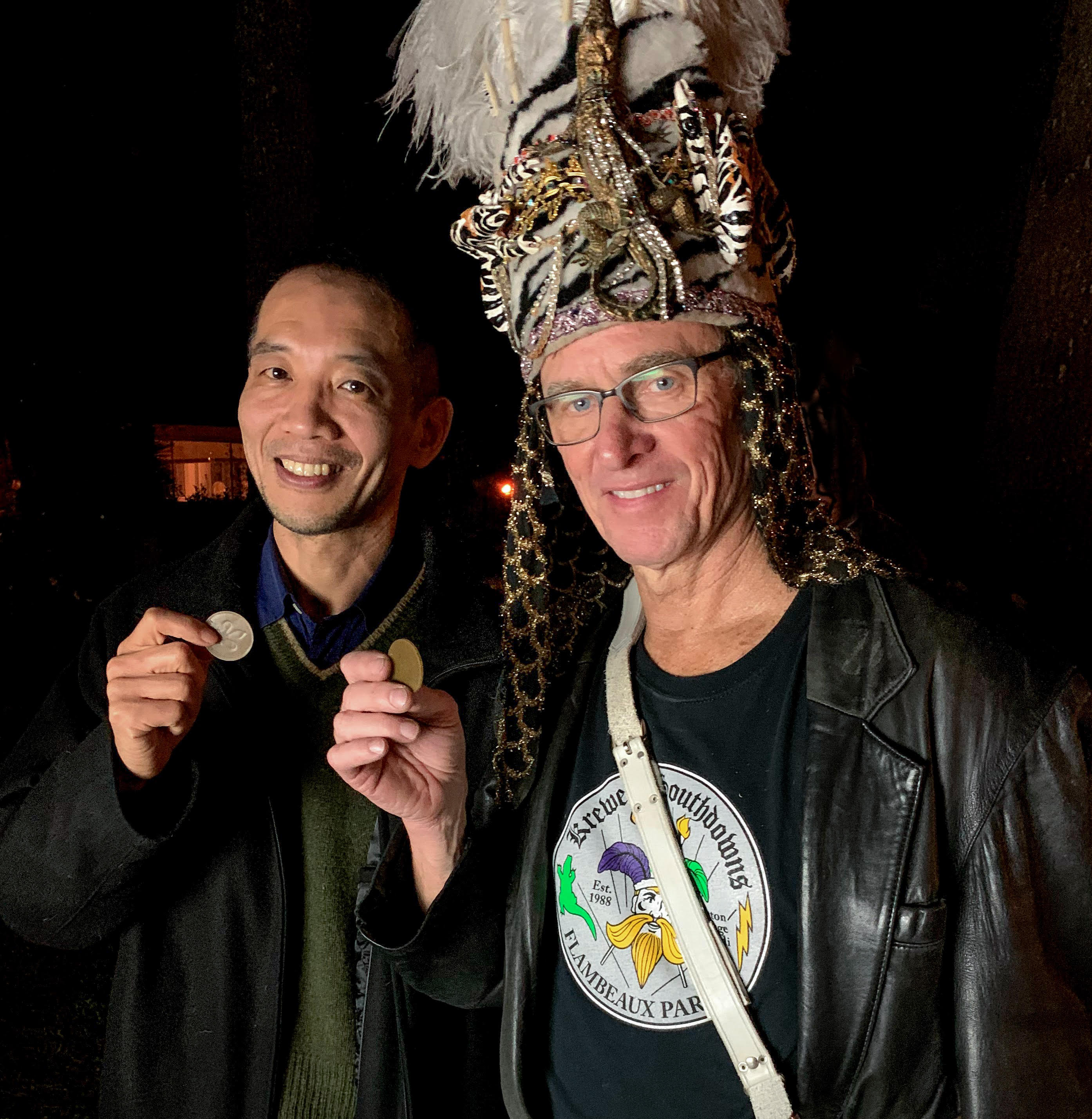 Two men face the camera: at left, Naohiro Kato, and at right, a Mardi Gras krewe leader wearing a headdress. Both hold small bioplastic doubloons.