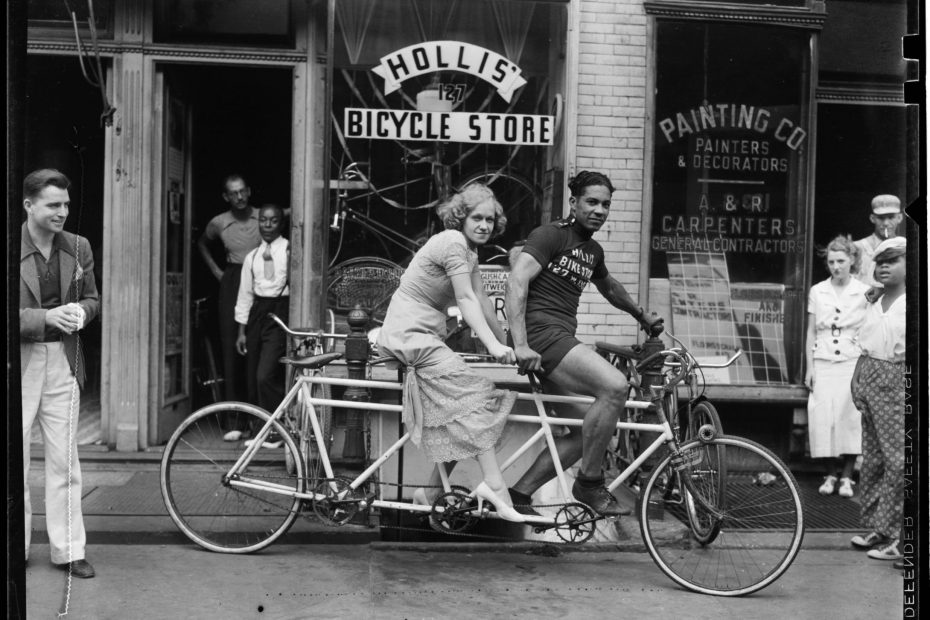 Photo shows a man and woman on a bicycle for two in the 1930s